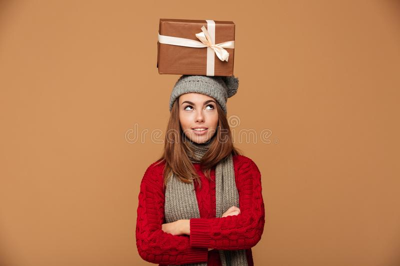 Thoughtful beautiful girl in winter clothes standing with crossed hands with gift box on her head, looking aside royalty free stock image