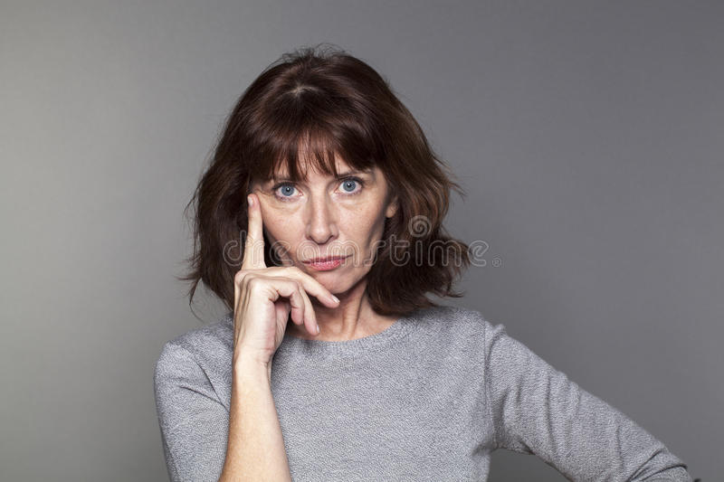 Thoughtful beautiful 50s woman in reflection stock photography