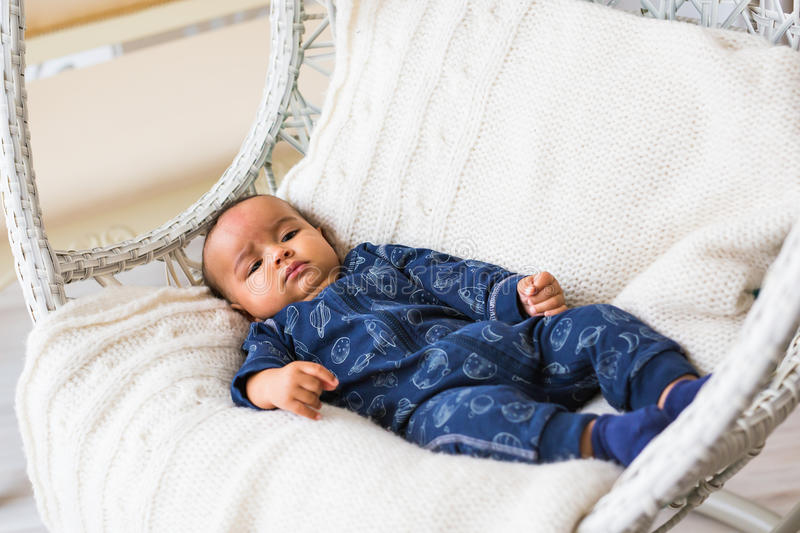 Thoughtful biracial mix of Hispanic and African American infant lying stock photo
