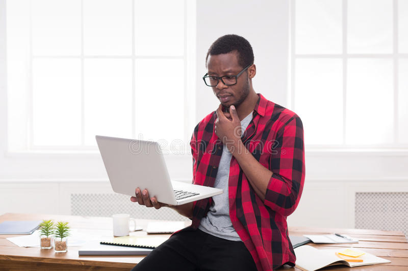 Thoughtful black businessman in casual office, work with laptop stock images