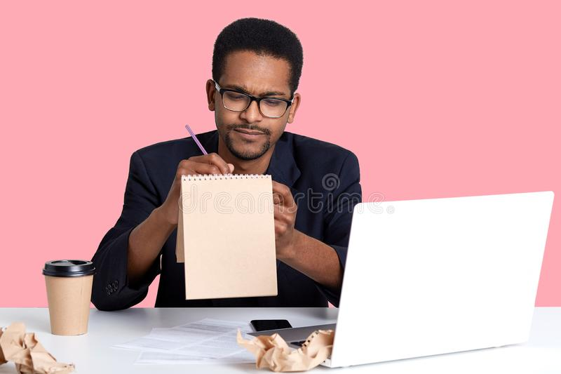 Thoughtful black businessman tries to write poem in notebook for her girlfriend while working on laptop. Handsom African American. Guy wears blak shirt and royalty free stock images
