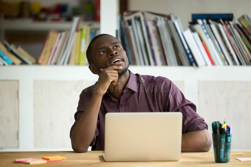 Thoughtful black worker dreaming about future achievements. African American office worker looking away thinking of problem solution while working at laptop stock images