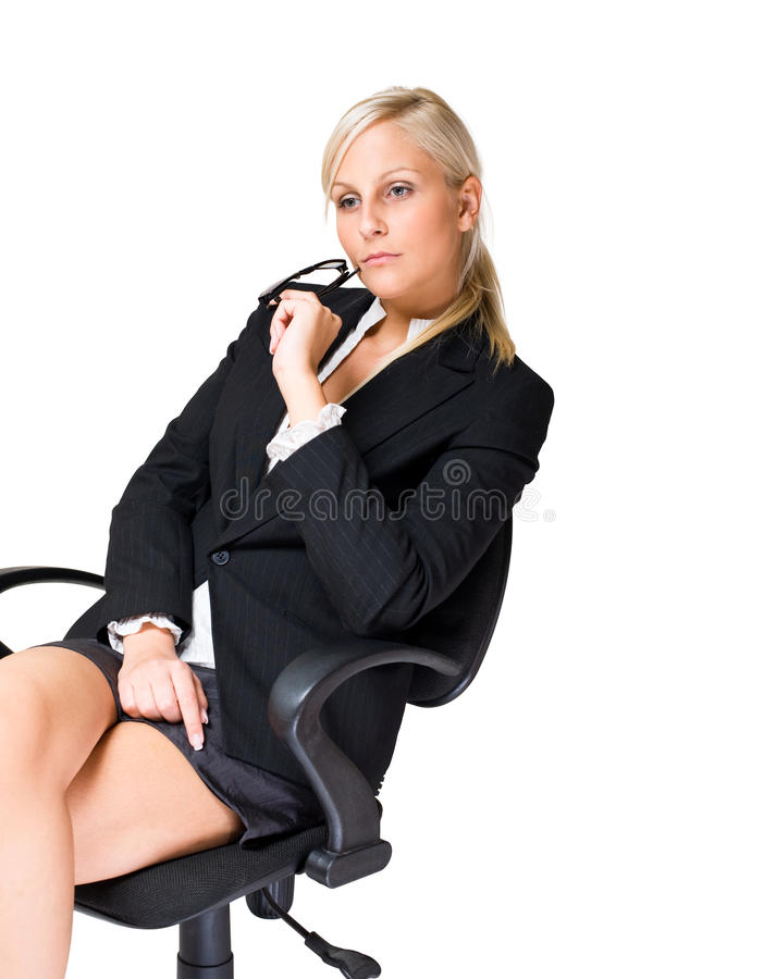 Thoughtful blond business woman. Thoughtful blond business woman sitting in office chair stock image
