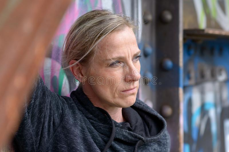 Thoughtful blond woman with a contemplative look. Standing against a colorful graffiti covered wall staring to the side in a close up portrait stock images
