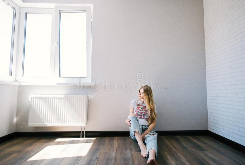 Thoughtful blonde girl sitting in a empty living room stock photos