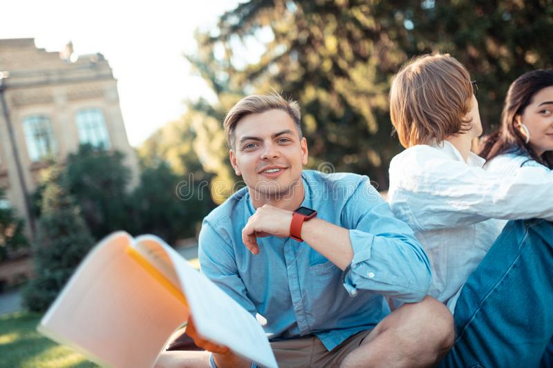 Thoughtful boy doing his homework near the university. Exercising outside. Thoughtful boy with a workbook in his hand doing his homework sitting with his royalty free stock photo