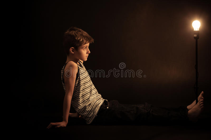 Thoughtful Boy Looking at the Light Bulb on Stand stock photo