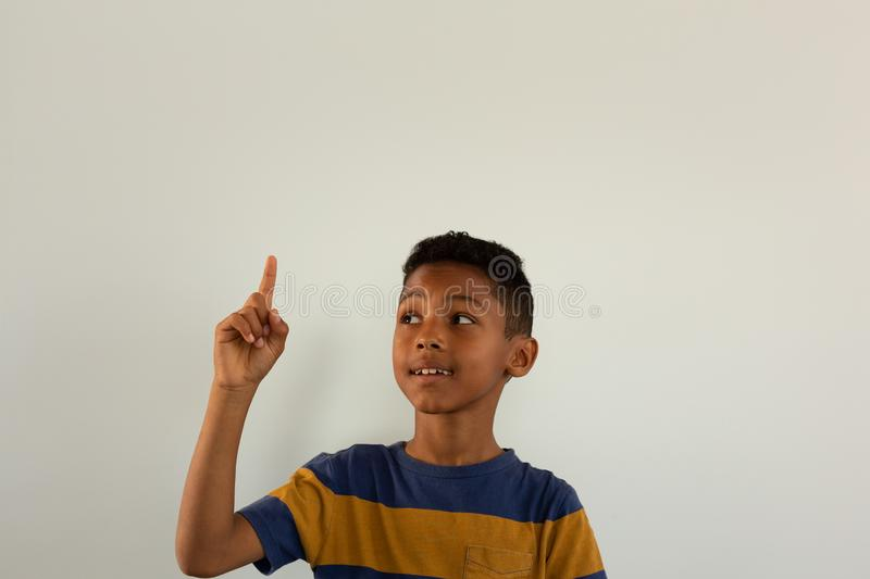 Thoughtful boy pointing his finger up while looking at his finger stock photo