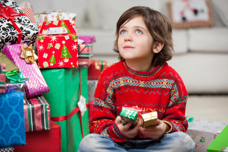 Thoughtful Boy Sitting By Christmas Gifts royalty free stock photo