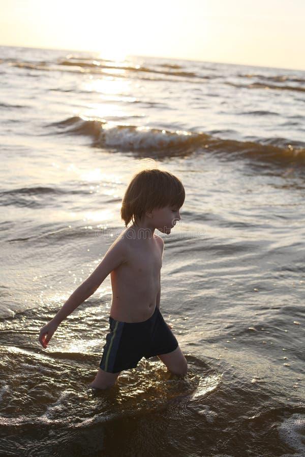 Free Thoughtful Boy Walking Knee Deep In The Sea Stock Photo - 42724520