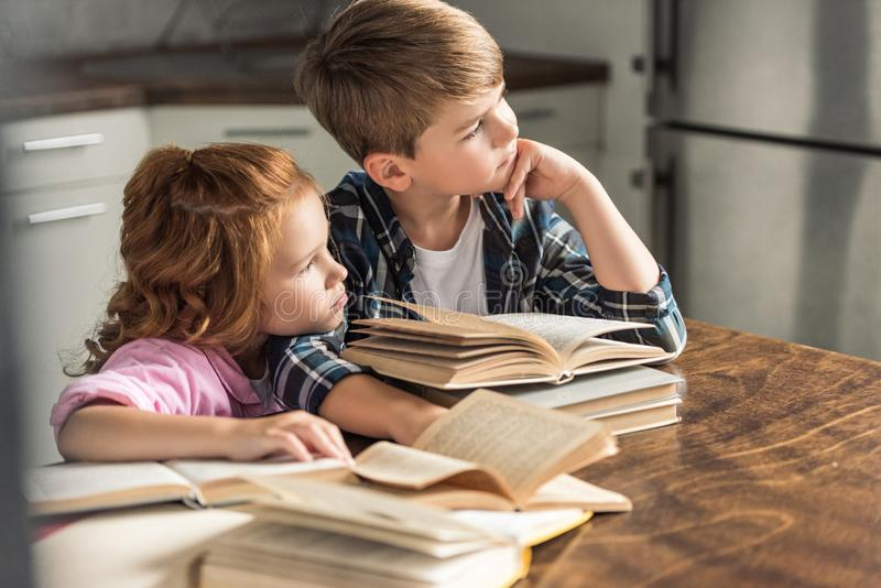 Thoughtful brother and sister sitting at table with pile of books. And looking away stock photos