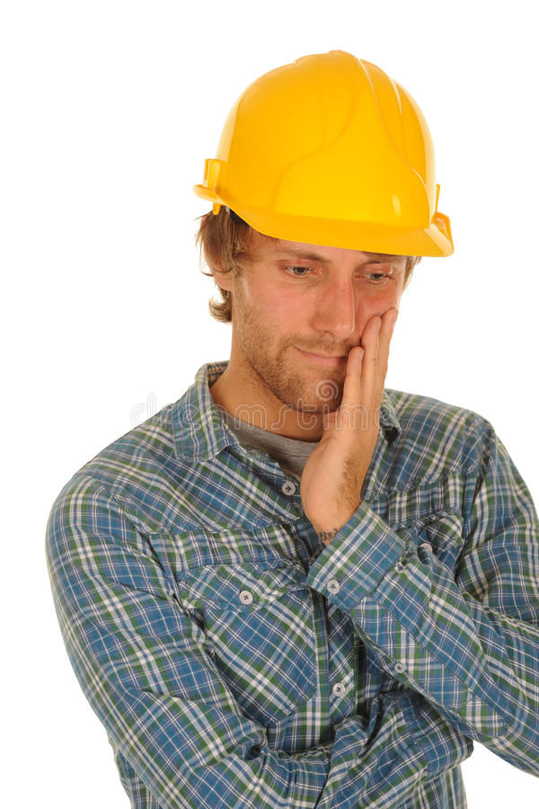 Thoughtful builder in hard hat. Half body portrait of thoughtful builder in check shirt with yellow hard hat royalty free stock images