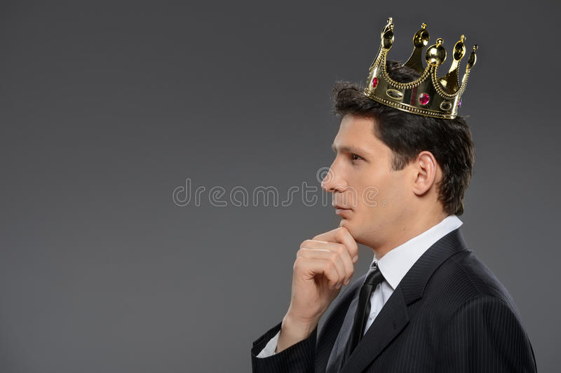Thoughtful business king. Side view of confident businessman thinking with his hand on chin royalty free stock photography
