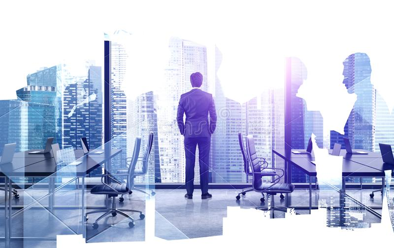 Thoughtful business leader in his office. Rear view of businessman looking at city from his panoramic office with his colleagues silhouettes. Concept of royalty free stock photo
