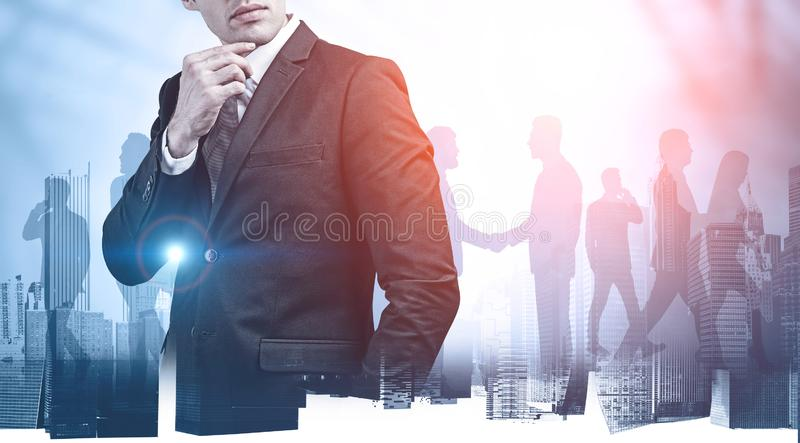 Thoughtful business leader and his team. Thoughtful young business leader with his diverse colleagues in background and double exposure of cityscape. Concept of royalty free stock photo