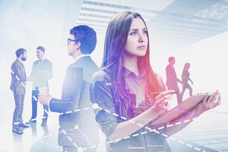 Thoughtful business people in city, trading. Thoughtful young business people working together with documents in modern city with double exposure of graphs stock photography