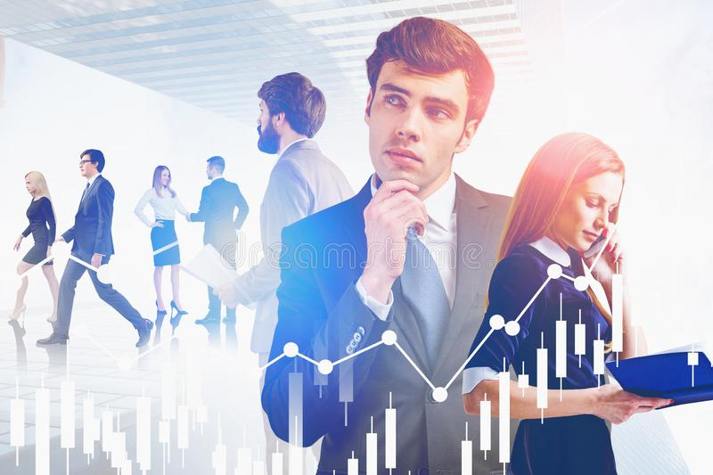 Thoughtful business team in city, charts. Portrait of young business people working together in modern city with double exposure of digital charts. Concept of stock photography