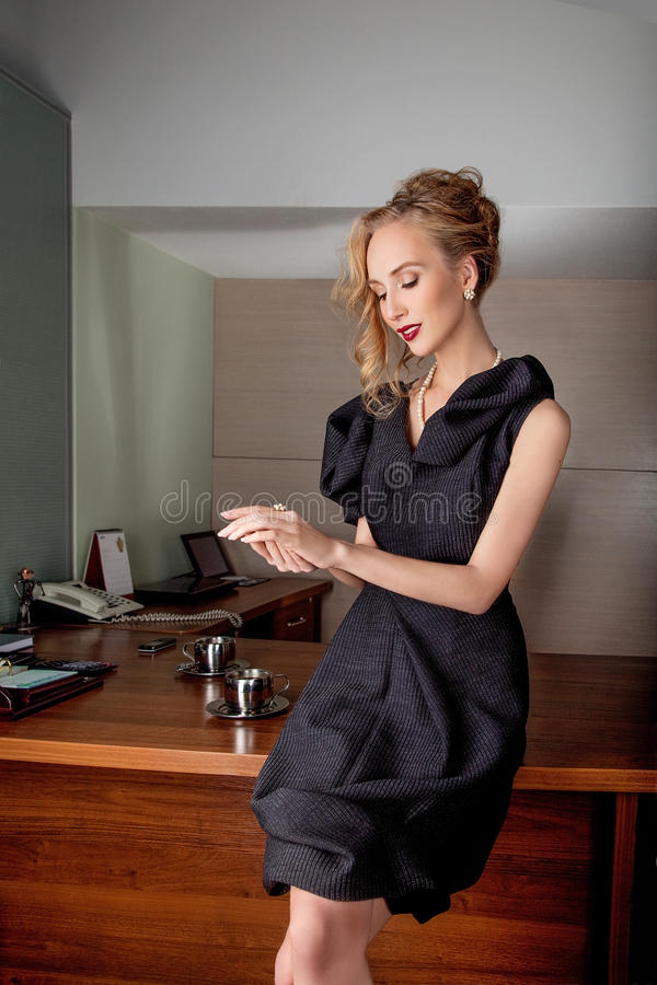 Thoughtful business woman fashion model in modern office indoors royalty free stock image