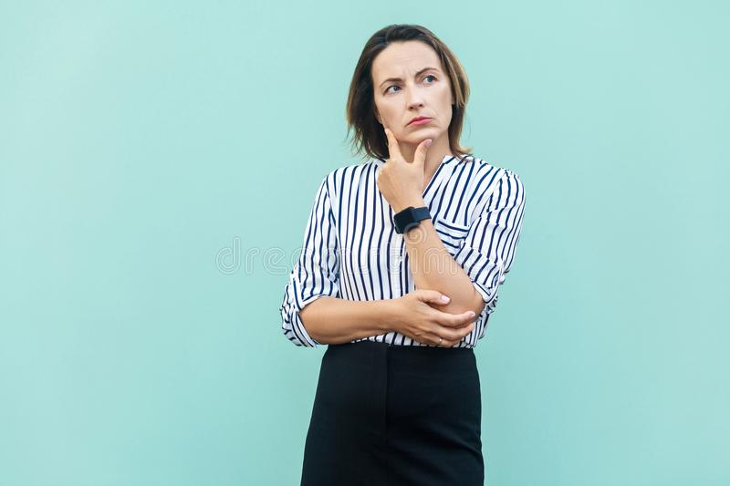 Thoughtful business woman looking away while standing against light blue wall. Studio shot royalty free stock photography