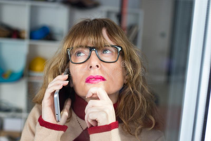 Thoughtful business woman with mobile stock photos