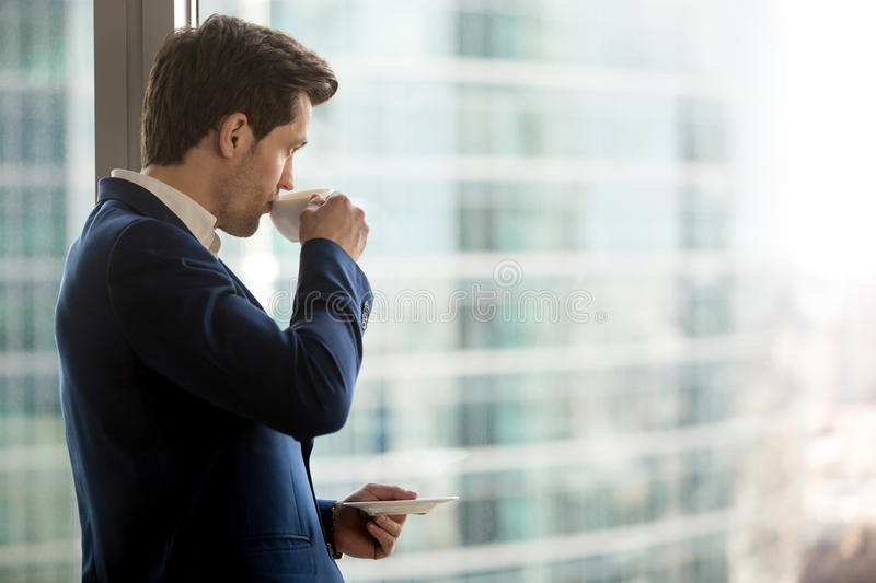 Thoughtful businessman drinking coffee, looking through office w royalty free stock image