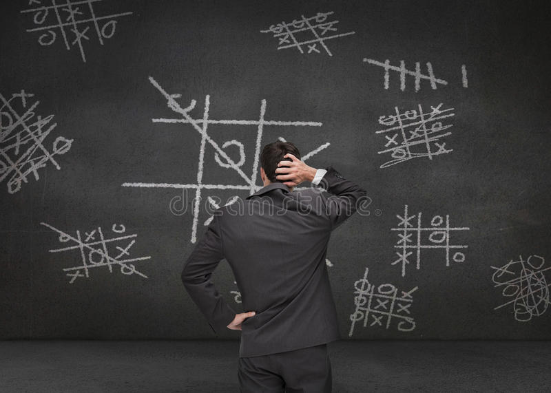 Thoughtful businessman looking at Tic-tac-toe game. Drawn on a chalkboard stock photography