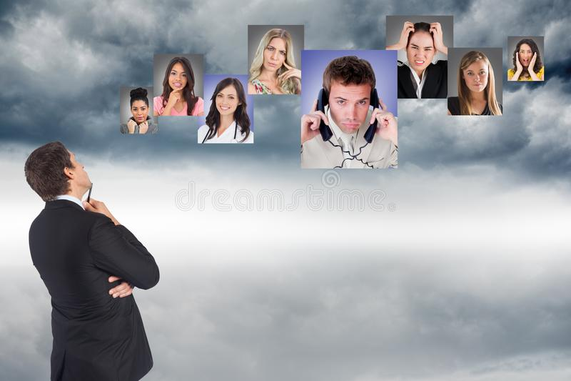 Thoughtful businessman looking at various candidates in sky stock image