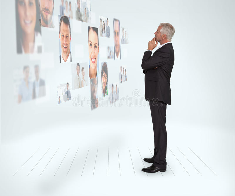 Thoughtful businessman looking at a wall covered by profile pictures stock photos
