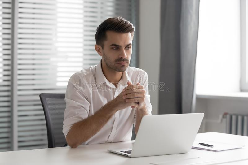 Thoughtful businessman lost in thoughts solve business challenge at workplace. Thoughtful businessman lost in thoughts at workplace, pensive professional think stock photography
