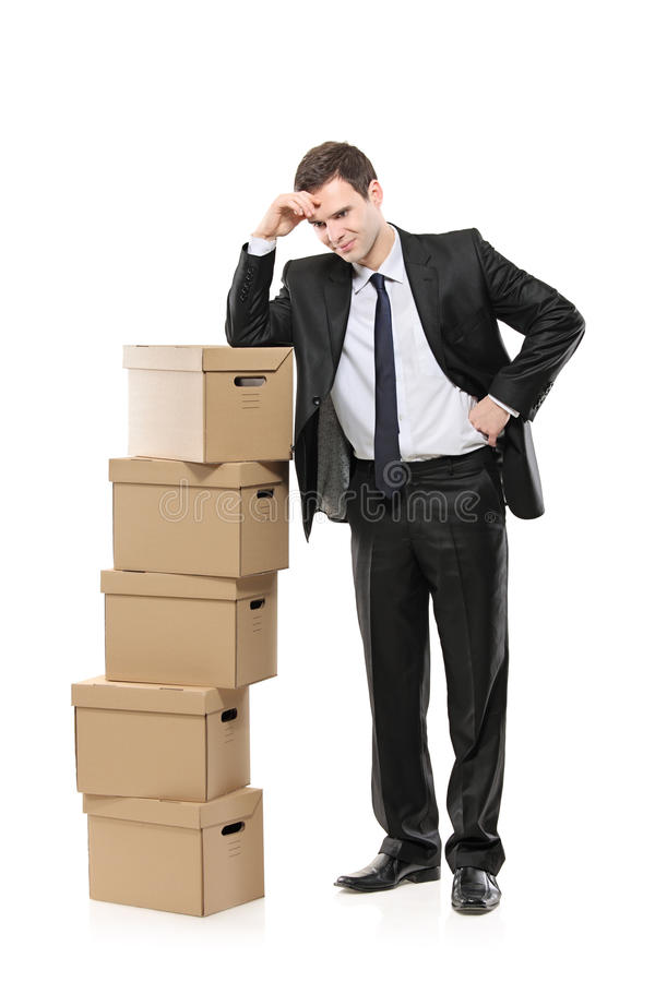 Thoughtful businessman with paper boxes stock images