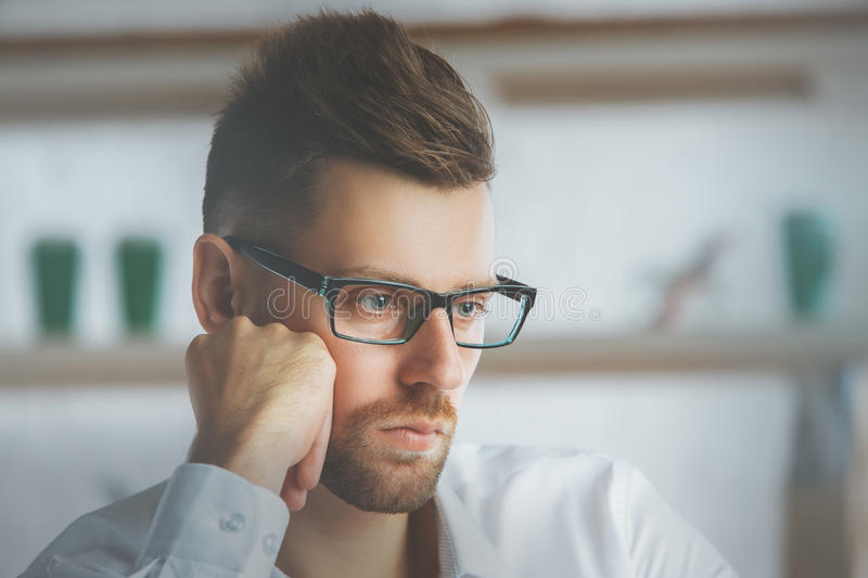 Thoughtful businessman portrait. Close up portrait of thoughtful european businessman with glasses at workplace stock photo