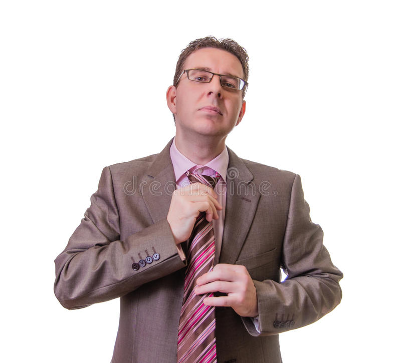 Thoughtful businessman putting his tie on white background stock image