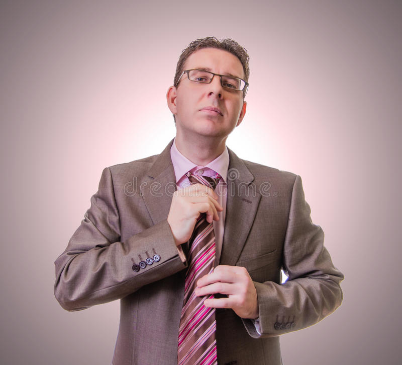 Thoughtful businessman putting his tie on white background royalty free stock image