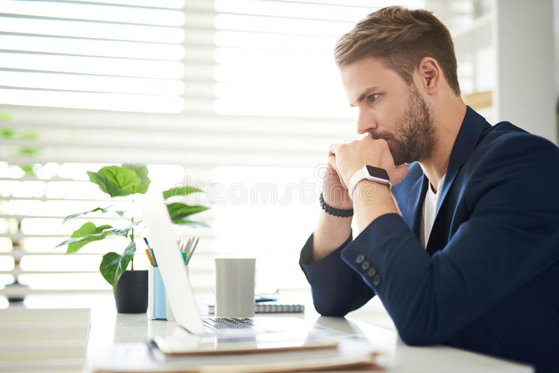 Thoughtful businessman sitting at computer stock photography