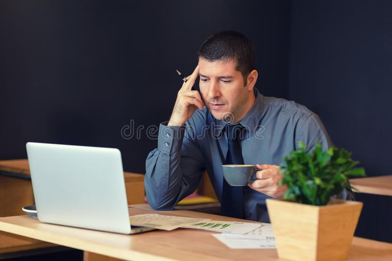 Thoughtful businessman sitting at table in trendy cafe working on laptop royalty free stock image