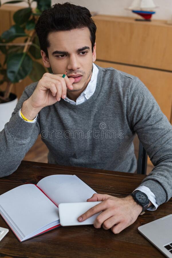 Thoughtful businessman with smartphone and pencil near notebook. At table stock photos