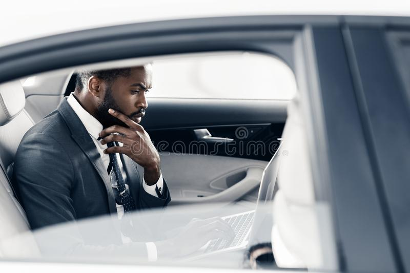 Thoughtful businessman working on laptop in car, copy space royalty free stock image