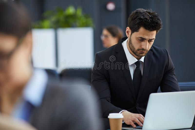 Thoughtful businessman working in lobby royalty free stock photo