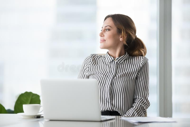 Smiling businesswoman thinking or dreaming distracted from work. Thoughtful businesswoman looking to side dreaming about future success, smiling female boss or royalty free stock photos