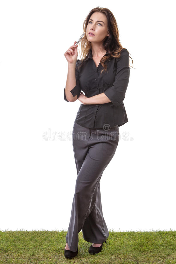 Thoughtful businesswoman with a pen. Pretty young business woman in a suit, standing on grass, holding a pen, looking thoughtful, isolated on white royalty free stock images