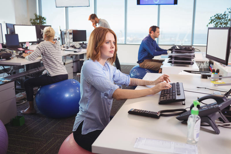 Thoughtful businesswoman sitting on exercise ball at office. Thoughtful businesswoman sitting on exercise ball at desk in office royalty free stock photography