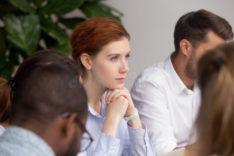 Thoughtful businesswoman thinking of business challenges opportunities at group meeting. Training, pensive dreamy women lost in thoughts sit with team at royalty free stock photo