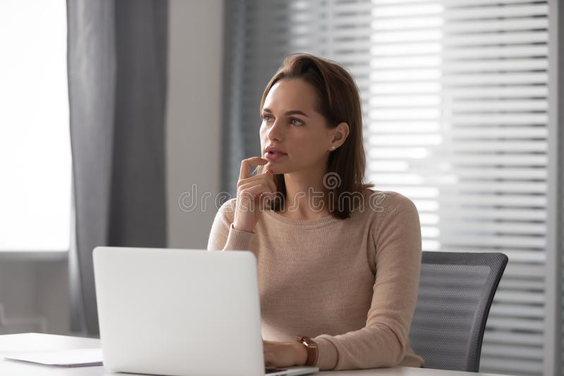 Thoughtful businesswoman using laptop, pondering online project, business vision royalty free stock photos