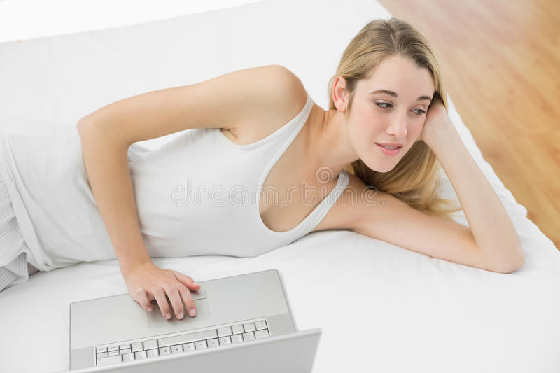 Thoughtful calm woman using her notebook lying on her bed stock photos