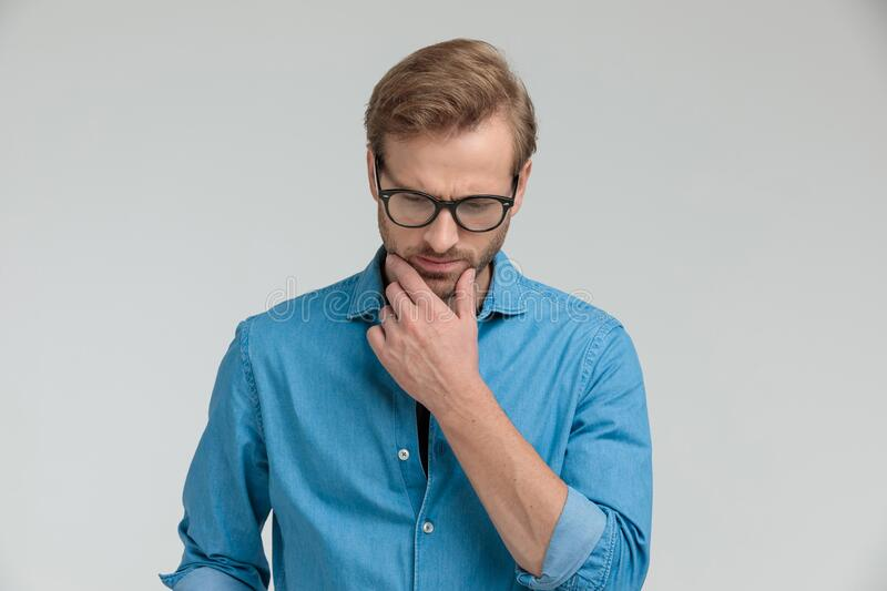 Thoughtful casual man holding hand to chin and thinking stock image