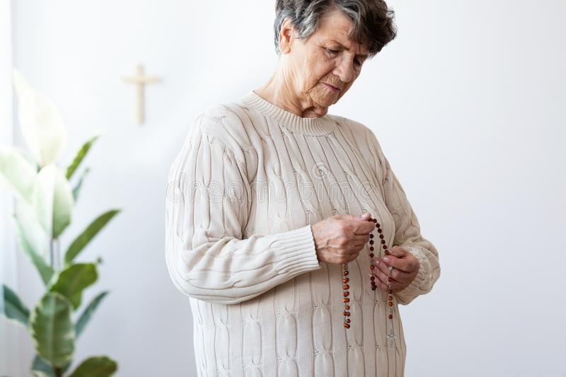 Thoughtful catholic elderly woman holding red rosary with cross royalty free stock photography