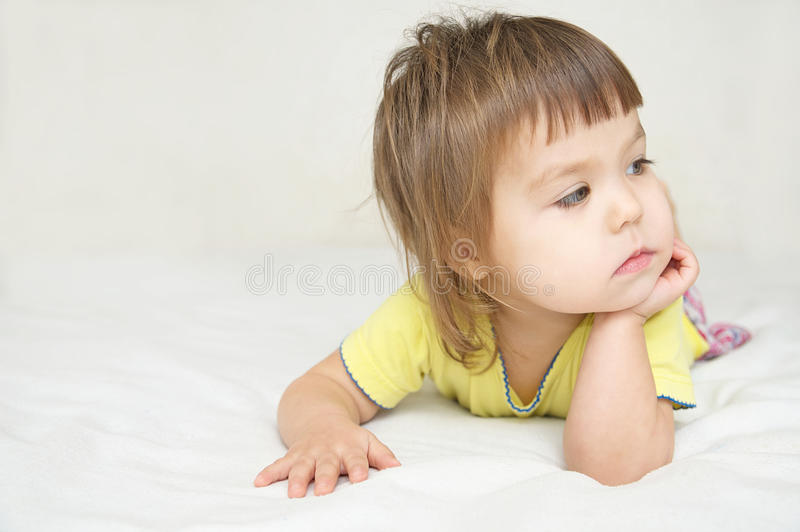 Thoughtful child , thinking Little girl lying on bed looking awa stock photography