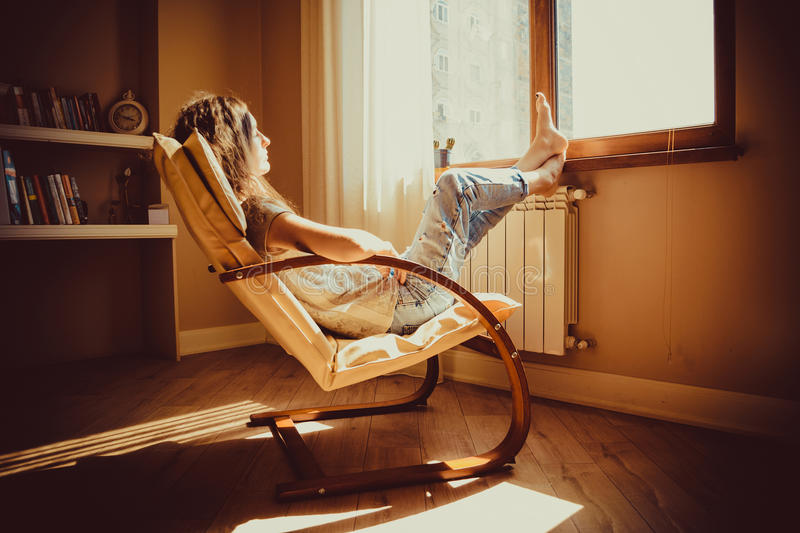Thoughtful concept. Sad woman lost in thought lounging in comfortable modern chair looking at window in livingroom. Warm natural l. Ight. Cozy home. Casual style stock photo