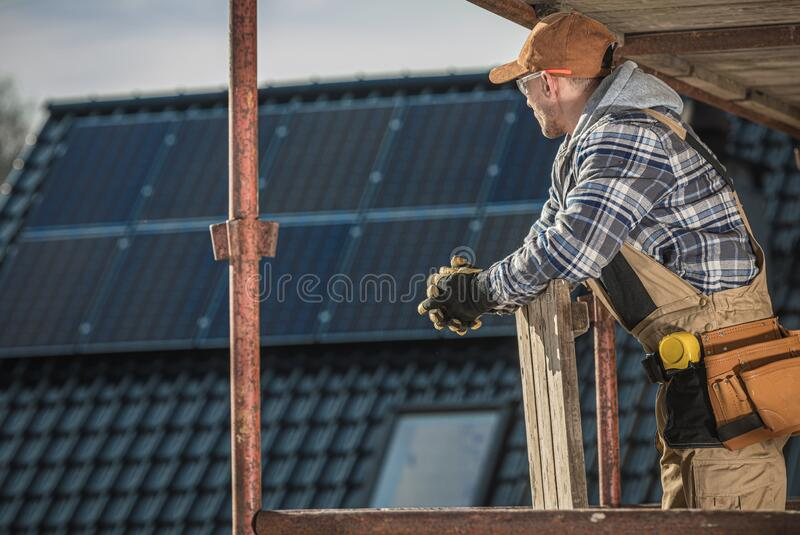 Thoughtful Construction Worker. On a Scaffolding During House Building. Industrial Theme royalty free stock images