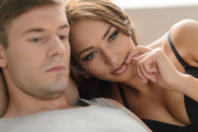 Thoughtful couple. Beautiful young couple lying close to each ot royalty free stock image